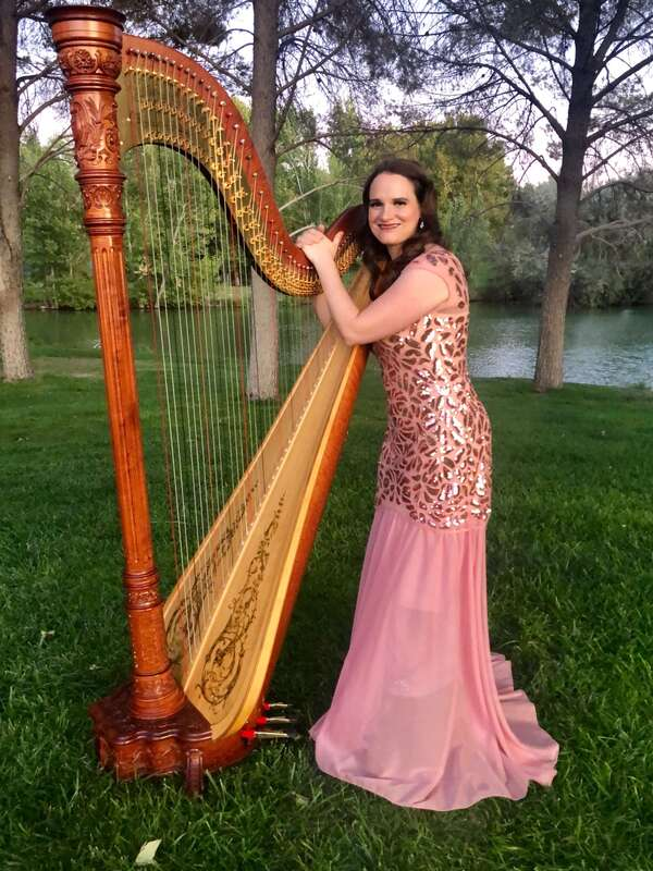 Harpist wearing a pink dress, standing with harp at Floyd Lamb Park by a lake